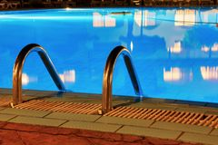 Blue water and handrails to enter the water. Pool at night. Blue water and handrails to enter the water royalty free stock photography