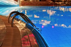 Blue water and handrails to enter the water. Pool at night. Blue water and handrails to enter the water stock images