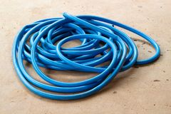The blue water hose lay down on the floor. The wet blue water hose lay down on the wet concrete floor stock images
