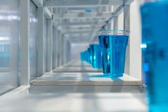 Blue water inside clear plastic cup on white metal shelf structu. Re for decoration. Installation art concept Royalty Free Stock Images