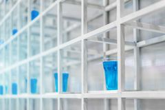 Blue water inside clear plastic cup on white metal shelf structu. Re for decoration. Installation art concept Royalty Free Stock Photography