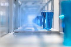 Blue water inside clear plastic cup on white metal shelf structu. Re for decoration. Installation art concept Stock Photo