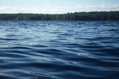 The blue water of the lake is rippling royalty free stock photos