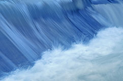Blue water in the movement. Blue water in movement, and the white foam Royalty Free Stock Photography