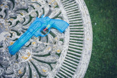 Blue water pistol on table in garden Royalty Free Stock Photos