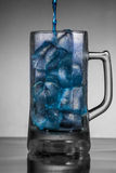 Blue water poured into iced mug. Product photography of water being poured in a ice mug Royalty Free Stock Photos