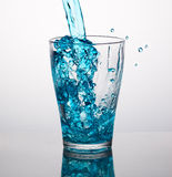 Blue water pouring into a glass Royalty Free Stock Images