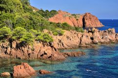 Blue water and red rocks of French Riviera stock image