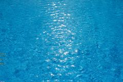 Water ripples texture in swimming pool with sunny glare. Blue water ripples texture in swimming pool with sunny glare Royalty Free Stock Photo