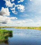 River with green sides under blue sky with clouds Royalty Free Stock Photography