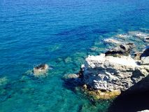 Blue water and rocks. View of a rocky shore and deep blue water Stock Photography