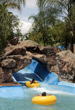 Blue water slide, stone grotto and swimming pool with children . Royalty Free Stock Photography