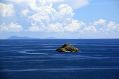 Blue water and small island Stock Images