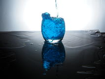 Blue water splash. Play with blue coloured water with flash Royalty Free Stock Photo