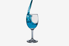 Blue water splash into wine glass Royalty Free Stock Images