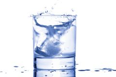 Blue water splashing out of a glass with drops Royalty Free Stock Photos