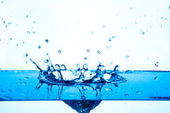 Blue water splashing on white background. Stock Photos