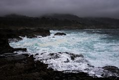 Blue Water in Stormy Surge against Rocky Shore in California. Stormy surf on rocky coast under cloudy skies in dramatic California coastal seascape stock photography