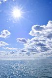 Blue water and sunny sky background stock images