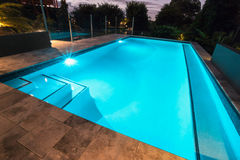 Blue water swimming pool with flashing lights with floor tiles Stock Photos