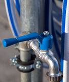 Blue Water Tap Closed. With striped hose in backdground Royalty Free Stock Photos