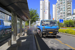 Blue water truck watering the green belt at bus station Stock Photos