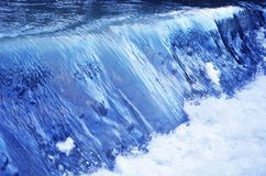 Blue water and a waterfall on the river. The blue water and long waterfall Royalty Free Stock Photos