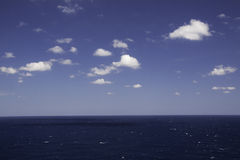 Blue Water and Waves, Blue Sky and White Clouds Royalty Free Stock Images