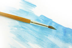 Blue watercolor and paintbrush. Blue watercolor and yellow paintbrush on a white paper stock photography