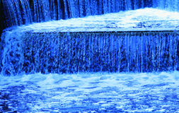Blue waterfall. Ornamental man-made waterfall with running water in shades of blue Stock Photography