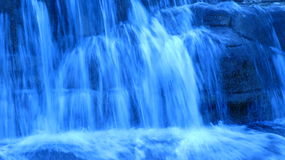 Blue waterfall. Blue toned image of an impressive waterfall royalty free stock photos
