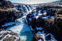Blue waterfall in the winter of Iceland. Flowing through a canyon stock photo