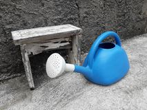 Blue watering can on a onld wall background. stock photo