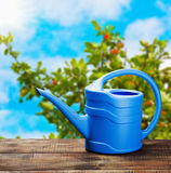 Blue watering can on the table Royalty Free Stock Photography