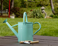Blue Watering Can on Table Outdoors Stock Photos