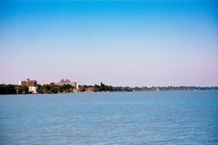 Balaton lake view in summer Siofok, Hungary with buildings on background. Blue waters of Balaton lake in Siofok Hungary on foreground. Clear blue sky in a sunny royalty free stock image