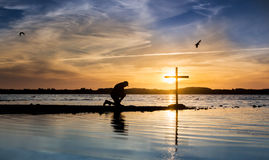 Blue Waters Cross. Cross at a lake with a man in prayer beside it, as the sun goes down Stock Photo