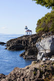Blue waters of San Juan island, Washington. Blue waters of coast of San Juan island, Washington state. Lime Kiln Lighthouse at Whale Watch Park in background royalty free stock photography