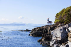Blue waters of San Juan island, Washington. Blue waters of coast of San Juan island, Washington state. Lime Kiln Lighthouse at Whale Watch Park in background stock images