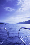 Blue waterscape from boat. Blue waterscape seen from a boat, focus on front waves, railing visible, picture taken on Loch Ness, Scotland, UK royalty free stock images