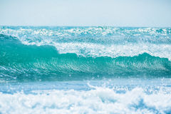 Blue wave in tropical ocean. Wave barrel crashing and sun light Royalty Free Stock Photo