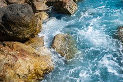 Blue waves break on the rocks of the shore stock image
