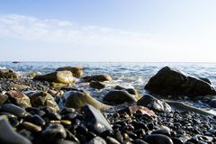 The blue waves crashing against the stones lying on the shore of the black sea royalty free stock images