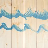 Blue waves drawn over the wood boards Royalty Free Stock Image