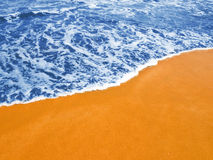 Blue waves on the gilded sand. ( High intensity of color Stock Image