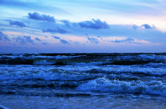 Blue waves. At sunset, driven by the salty wind and dramatic skies Stock Photo