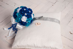 Blue wedding bouquet and wedding rings on a pillow. Wedding, bouquet, pillow, flower, ring, blue, decoration, floor, white, board, cloth, Blue wedding bouquet Royalty Free Stock Image