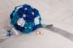 Blue wedding bouquet and wedding rings on a pillow. Wedding, bouquet, pillow, flower, ring, blue, decoration, floor, white, board, cloth, Blue wedding bouquet Stock Photo