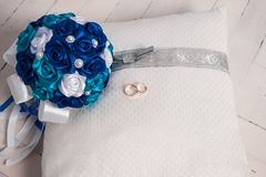 Blue wedding bouquet and wedding rings on a pillow. Wedding, bouquet, pillow, flower, ring, blue, decoration, floor, white, board, cloth, Blue wedding bouquet Stock Photos