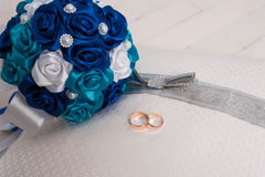 Blue wedding bouquet and wedding rings on a pillow. Wedding, bouquet, pillow, flower, ring, blue, decoration, floor, white, board, cloth, Blue wedding bouquet Stock Image